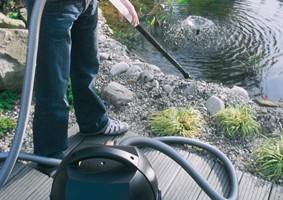 Onderhoud van een vervuilde vijver door een vijverstofzuiger